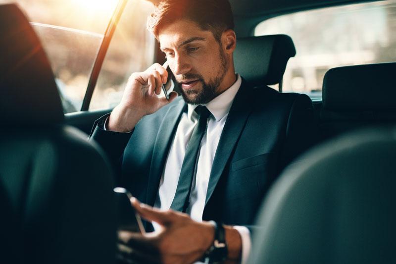 Jovem empresário falando no telefone celular e usando tablet pc enquanto sentado no banco de trás de um carro