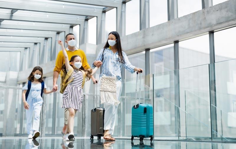 Família com dois filhos saindo de férias, usando máscaras faciais no aeroporto.